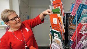 Kvinna visar broschyrer för olika cancerrehabilitering