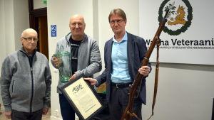 Miehet esittelevät kivääriä ja palkintopokaalia