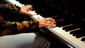 någon spelar på ett piano