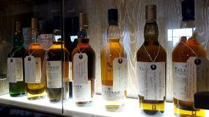 Whiskeyflaskor av märket Talisker uppradade på en upplyst hylla.