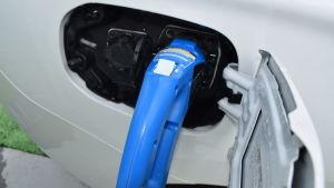 Hybridbil laddas vid en affär.