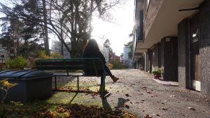 Kvinna i motljus som sitter på bänk