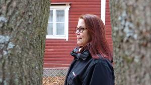 Rödhårig kvinna i profil mot röd husvägg