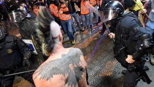 Kravallpolis angriper en demonstrant under natten kravaller i Barcelona