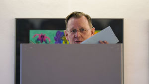 Bodo Ramelow står i ett valbås och visar upp sin röstsedel.