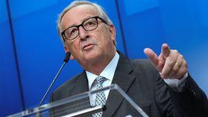 En kostymklädd Jean-Claude Juncker står bakom ett podium och talar i en mikrofon.