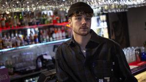 Lucas står lutad mot en bardisk och ser rakt in i kameran med mössa på.