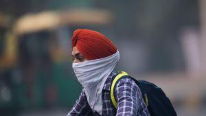 En man som rör sig i trafiken i New Delhi skyddar sig mot luftföroreningar 4.11.2019