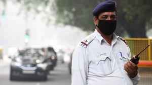 En polis med andningsskydd i New Delhis smog 2.11.2019
