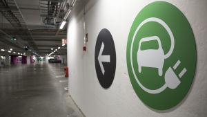 Sähköautojen latausparkeihin osoittava kyltti Triplan parkkihallissa