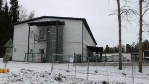 En vit dagisbyggnad i snöigt landskap.