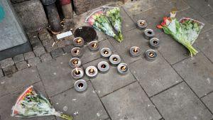 Rosor tillsammans med tända marschaller utgör initialerna AJ utanför pizzerian där 15-åringen sköts till döds på lördag.