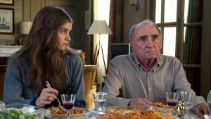 mies ja nuori nainen istuvat ruokapöydässä. Nainen katsoo miestä, mies katsoo eteenpäin.
