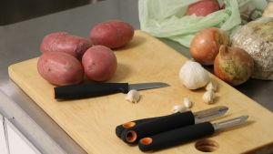 Ett skärbräde med några potatisar, en vitlök och några lökar samt en liten kniv och två skalknivar.