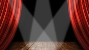 Röda gardiner och ljuskäglor på en teaterscen.