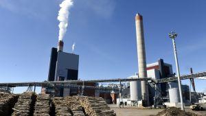 Papperasfabrik i Kouvola med rök ur skorstenar och stockhögar som väntar.