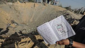 En släkting till dödsoffren visar upp ett skolhäfte som hittades i gropen efter den israeliska flygräden mot Rasmi Abu Malhous i Deir al-Balah.
