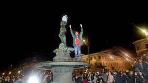 En man står på statyn Havis Amanda med armarna uppsträckta i luften.