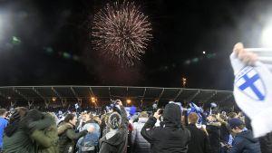 Fans som står på fotbollsplan och ser på fyrverkerier samtidigt som de firar Finlands vinst i matchen mot Liechtenstein som tog dem till EM 2020.