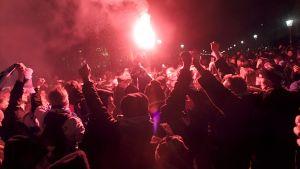 Hela bilden fylls av fans, vissa har händerna upp i luften och rök gör att bilden färgas röd och svart.