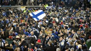Ett myller av människor. Många med Finlands färger på mössa eller halsduk. En person håller i Finlands flagga.