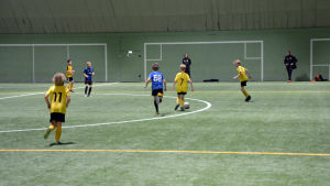 Fotbollsspelare från åifk p11-laget och FC Inter spelar fotboll på en fotbollsplan inomhus.