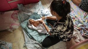 Nainen pukee pientä, lattialla makaavaa vauvaa.
