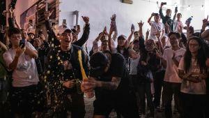 Firande oppositionsanhängare öppnar en champagneflaska utanför en vallokal i Hongkong