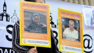 En kvinna håller upp bilder av de personer som åtalas för sexuella övergrepp på barn.