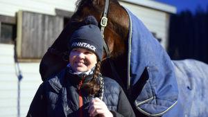 Nina Pettersson-Perklén står och håller i hästen Emil.