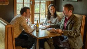 Inspelningsbild från Knives Out. Chris Evans, Ana de Armas sitter vid ett cafébord och regissören Rian Johnson ger dem instruktioner för nästa scen.