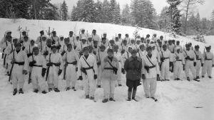 Lumipukuun pukeutuneita sotilaita rivissä aseet olalla talvella