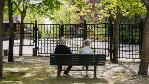 Kaksi vanhusta istuu selin puistonpenkillä, katsellen kadulle päin. Ympärillä puita, joissa juuri puhjenneita lehtiä.
