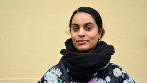 en kvinna med pakistanskt ursprung står framför en gul vägg iklädd svart tjock halsduk och blommig tjock jacka.