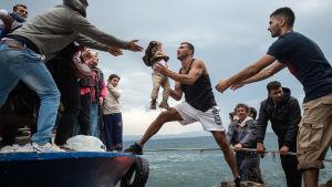 Mies ottaa veneestä vastaan lasta.