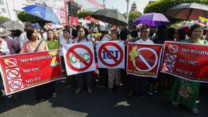 Människor i Rangoon med plakat där det står att man motsätter sig både rohingyer och den internationella domstolen i Haag