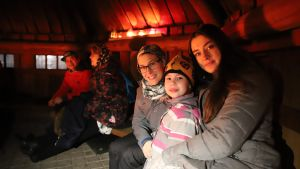 Ulkomaalainen opiskelija on ystäväperheen äidin ja 7-vuotiaan tytön kanssa kodassa iltanuotiolla.