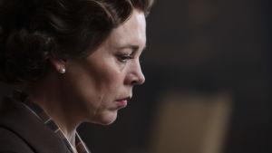 En medelålders kvinna med pärlörhängen i profil mot en mörk bakgrund.