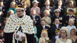 En ung man i hermelinpäls och en gyllne krona står på ett podium framför en mikrofon. I bakgrunden syns en festklädd publik.