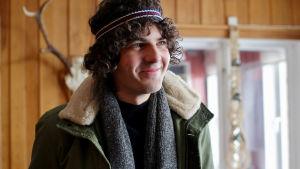 Karaktären Peter i lockigt mörkt hår ler stort.