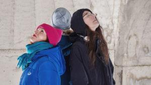 Tre personer med ryggarna mot varandra inuti en kupolformad byggnad av betong.