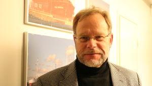 En medelålders man med kort ljust hår och glasögon står intill en vägg.