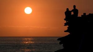 Två människor ser på solnedgången vid Bronte Beach i Sydney
