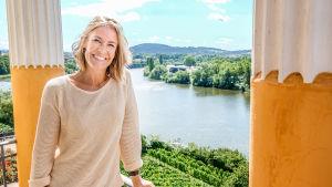 Ella Kanninen hymyilevänä aurinkoisella parvekkeella Pohjois-Italiassa. Ohjelma on Ellan matkassa: roomalaisten jäljillä.