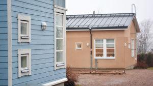 Ett blått trähus och ett brunt rappat hus står på en gård. I det bruna husets fönster finns julljusstakar.