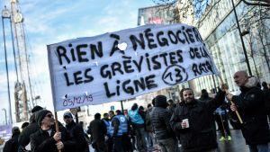 Metroarbetare i Paris demonstrerar med plakat på julafton.