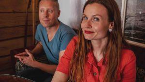 Niklas Aldén sinisessä t-paidassa istuu punapaitaisen Hannamari Hoikkalan vieressä hirsimökissä.