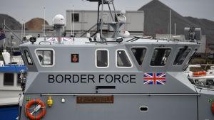Rannikkovartioston alus, jonka kyljessä on Britannian lippu ja pelastusrengas.
