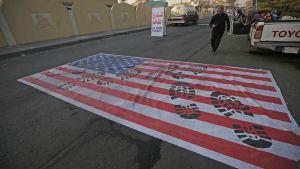 USA:s flagga ligger på vägen i Bagdad i Irak efter USA:s flygattack mot högt uppsatta ledare i Mellanöstern.