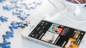 Älypuhelin pöydällä, näytöllä näkymä Yle Areenasta. Pöydällä myös nappikuulokkeet ja palapelin palaisa,
